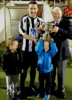 Barry Fitzgerald, St. John Bosco, receives the St Michael's Cup from Denis Lyne, Cork AUL