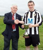 St. John Bosco A captain, Barry Fitzgerald, being presented with the League 1A trophy by Ted O'Mahony, Cork AUL